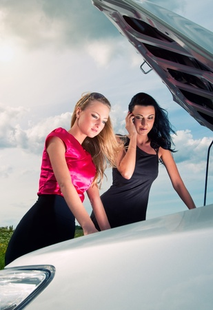 Two young women with broken car on a road Stock Photo - 11081726