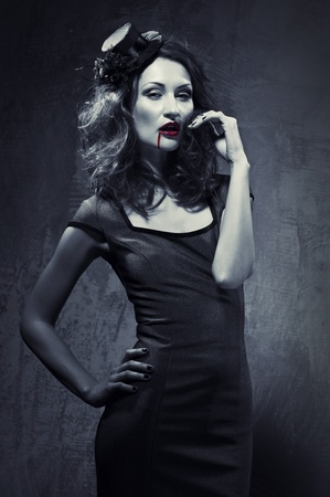 Black and white photo of seductive woman with blood on her lips photo