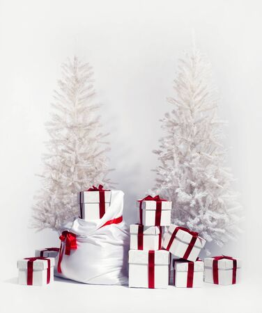 Christmas trees with heap of gift boxes over white background photo