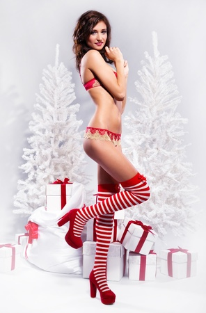 Beautiful brunette wearing sexy lingerie posing over christmas background photo