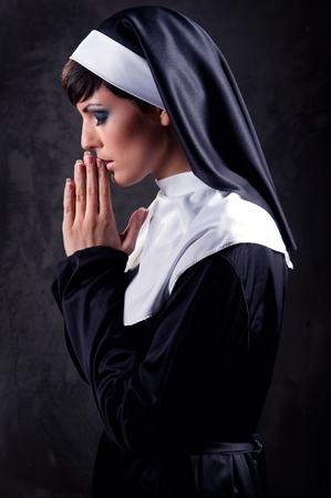 Young attractive nun praying photo