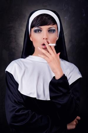 sinner: Smoking young nun Stock Photo