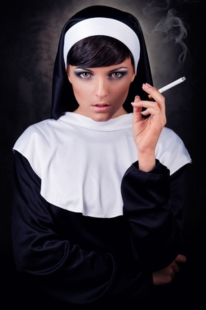 provocative: Smoking young nun Stock Photo