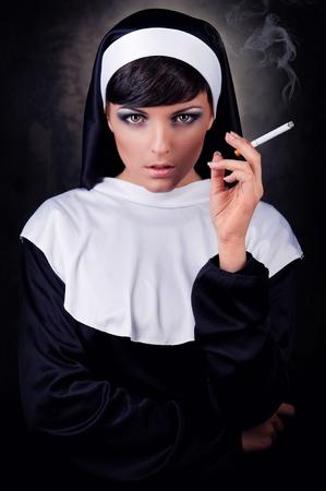 nun: Smoking young nun Stock Photo