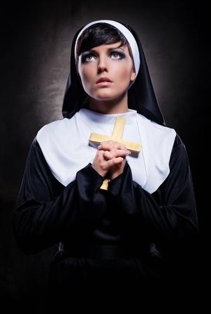 nun: Young attractive nun holding a cross Stock Photo
