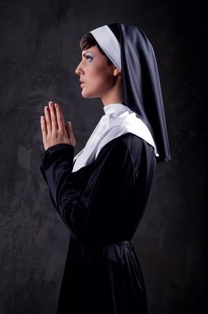 black nun: Young attractive nun praying