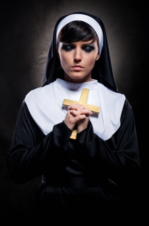 Young attractive nun holding a cross photo