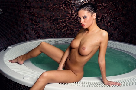 Beautiful naked woman relaxing in jacuzzi Imagens