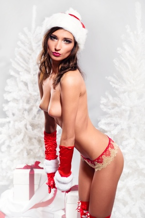 naked female: Beautiful naked female wearing christmas hat and gloves posing over winter background Stock Photo