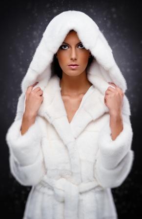 Beautiful woman in white fur coat photo