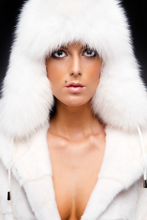 Beautiful woman in white fur coat and cap Stock Photo - 11958881