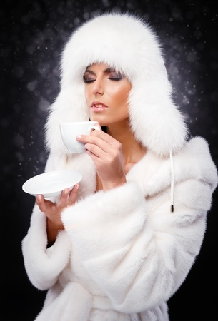 Beautiful woman in white fur coat and cap drinking coffee  photo