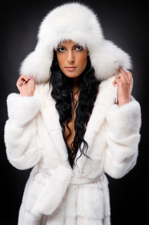 Beautiful woman in white fur coat and cap photo
