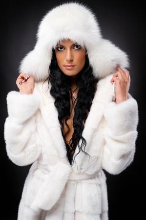Beautiful woman in white fur coat and cap photo