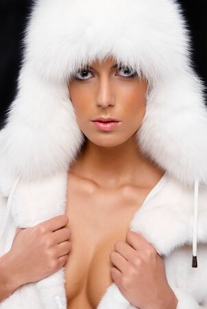 Beautiful woman in white fur coat and cap Stock Photo - 11958887