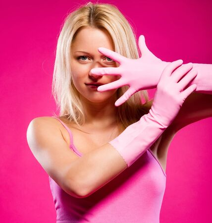 Woman wearing rubber gloves posing over pink background Stock Photo - 11958886