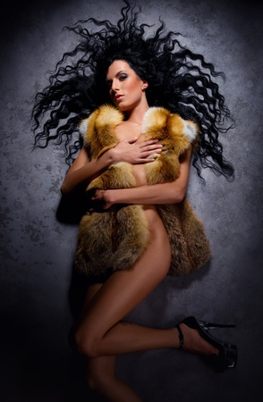 Gorgeous naked brunette wearing fur vest lying indoors photo