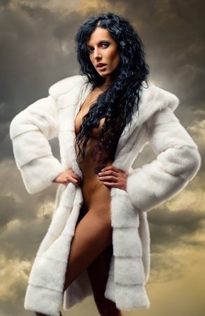 Gorgeous naked brunette wearing white fur coat posing over clouds photo