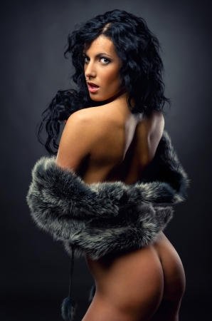 Gorgeous naked brunette wearing fur coat  posing indoors photo