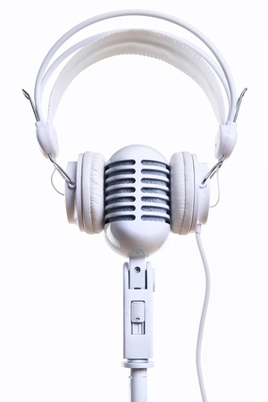 White vintage microphone and headphones over white background photo