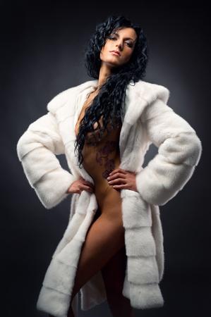 Prachtige sexy brunette draagt witte bontjas poseren binnenshuis