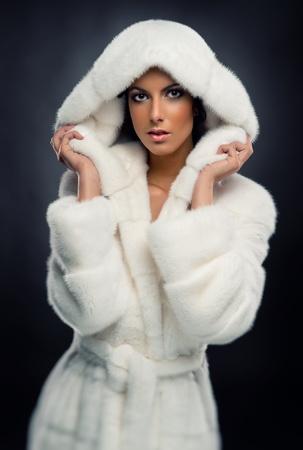 Gyönyörű nő, fehér divatos bundában