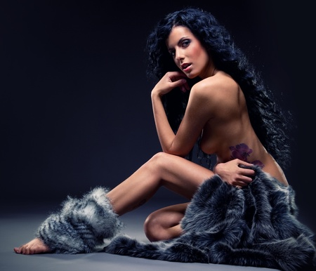 nude girl sitting: Gorgeous sexy brunette in fur posing indoors