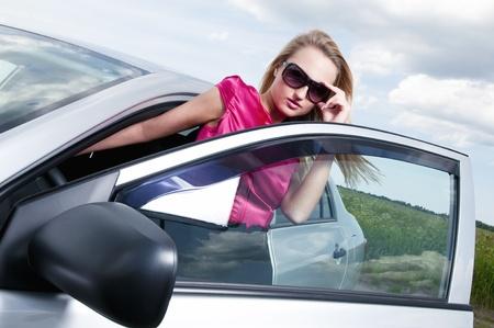 Young beautiful woman posing near the car photo