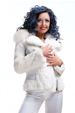 Beautiful brunette in white fur coat posing over white background photo