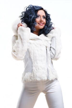 Cheerful brunette in white fur coat posing over white background photo