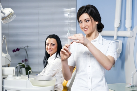 nurse injection: Attractive woman dentist with medical syringe and smiling patient in the dental clinic