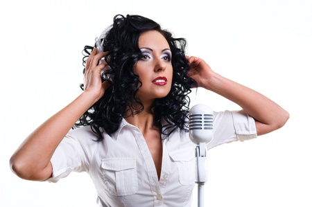 Beautiful young woman with headphones and microphone over white background photo