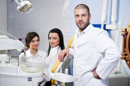 stomatology: Friendly male dentist, assistant and smiling patient at dental clinic