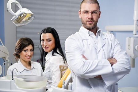 Friendly male dentist, assistant and smiling patient at dental clinic photo