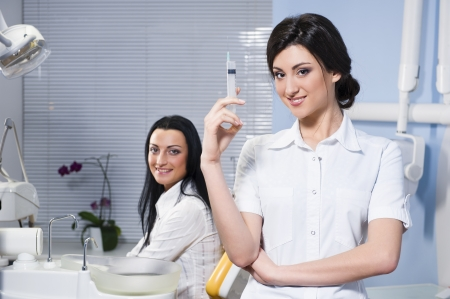 Attractive woman dentist with medical syringe and smiling patient in the dental clinic photo