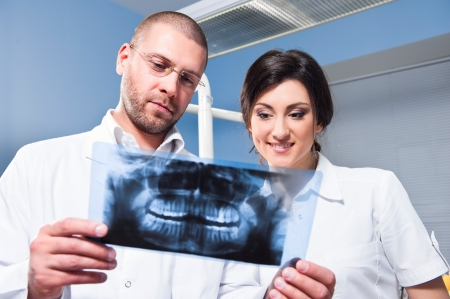 Dentist and assistant checking x-ray at dental clinic photo