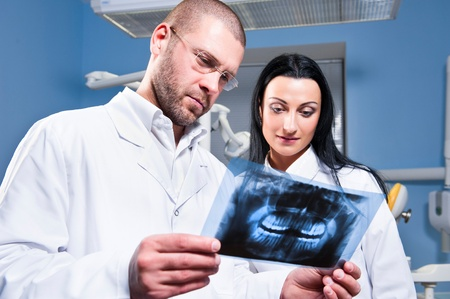 roentgenogram: Dentist and assistant checking x-ray at dental clinic