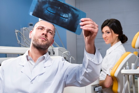 roentgenogram: Dentist with x-ray and smiling patient in the background