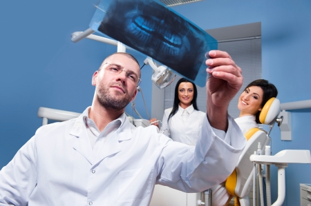 male dentist: Dentist with x-ray and smiling patient and assistant in the background