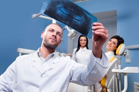 Fogorvos röntgen és mosolyogva türelmes és asszisztens a háttérben Stock fotó
