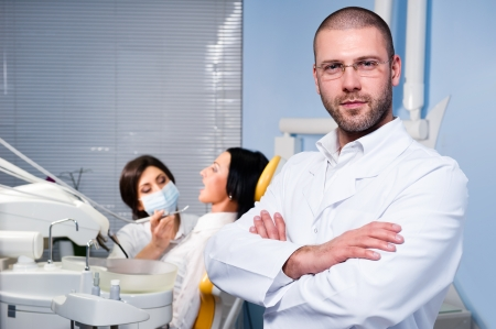 male dentist: Friendly male dentist with assistant and patient at dental clinic Stock Photo