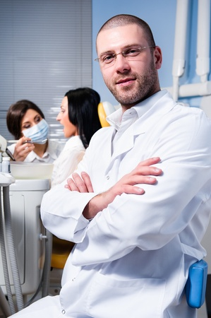 Friendly male dentist with assistant and patient at dental clinic photo