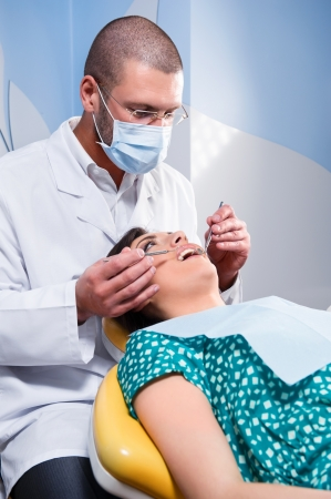 Female patient having her teeth examined by specialist  photo