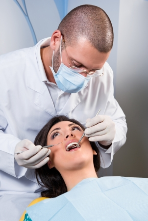 Female patient having her teeth examined by specialist Imagens