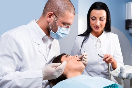 dental tools: Male dentist with assistant and patient at dental clinic Stock Photo