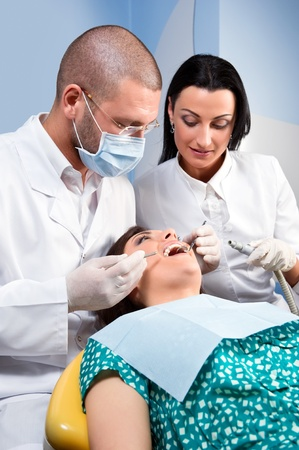 Male dentist with assistant and patient at dental clinic photo