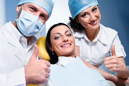 medical assistant: Friendly male dentist with assistant and smiling patient showing thumb up