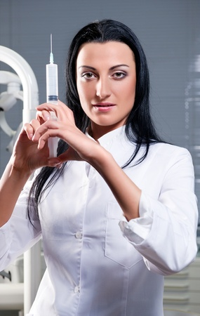 Attractive woman with medical syringe photo