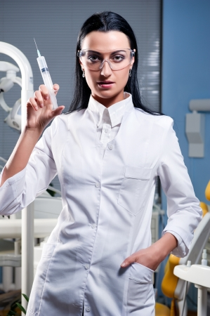 Attractive female doctor with medical syringe photo