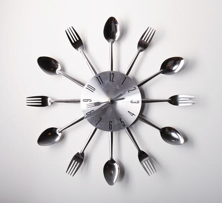 Clock-Design mit Löffel und Gabel über weißem Hintergrund Standard-Bild